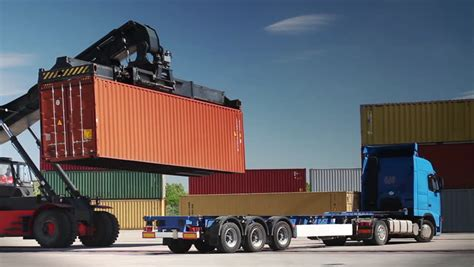 Container Handler Loading A Truck In Port Terminal