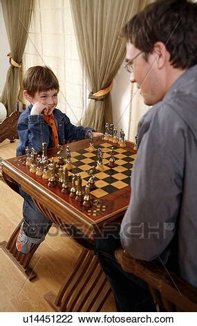 Stock Photo of Young man and little boy playing chess